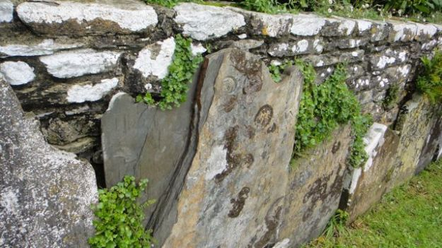 Ancient walls lined with ancient gravestones.