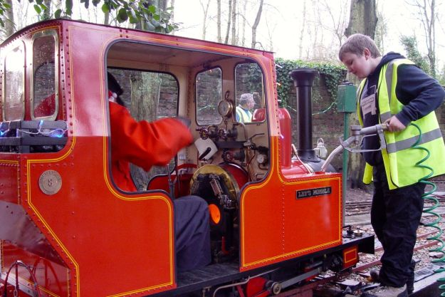 Stoking the fire, filling up the water. A real miniature steam engine.