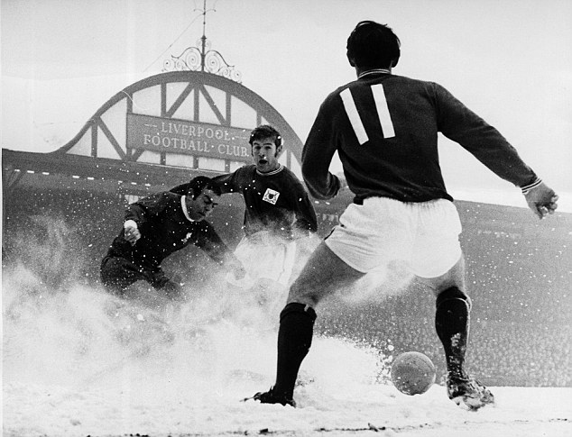 Ian St John of Liverpool emerges from the snow between two Nottingham Forest players.