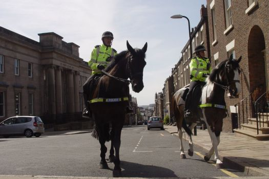 Sitting at the top of Mount Street watching the horses pass by.