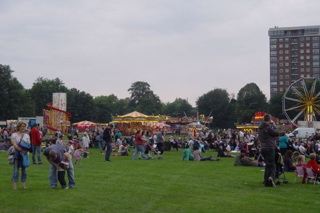 Children are happily gambolling about and the funfair's going in the distance.