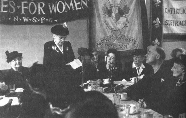 Eleanor Rathbone speaking in 1943. A wonderful picture, the people in the room clearly knowing they are in the presence of someone special. Nancy Astor id third from right.