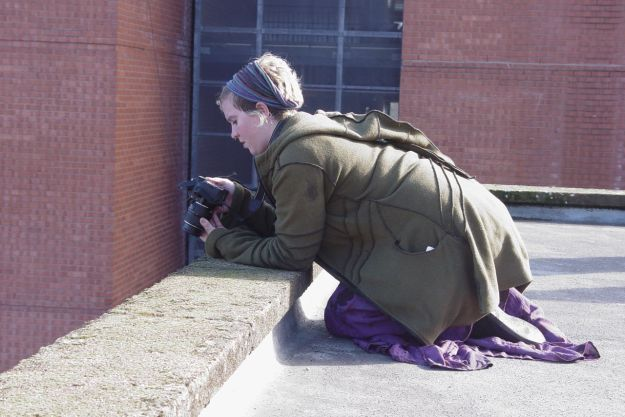 Jen kneels on the edge of the roof to capture something sacred.