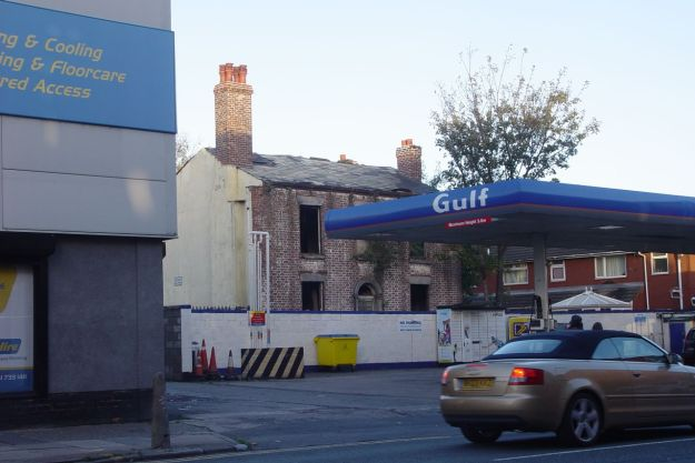 Ancient empty house behind a petrol station.