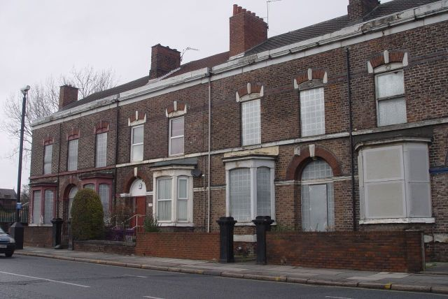 Opposite a row of splendid but empty homes.
