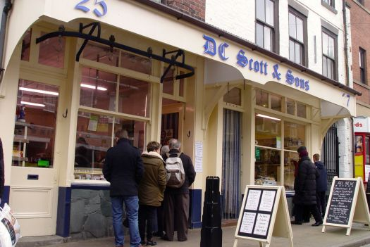 A shop in two halves. They're queuing at the butcher's. And in the other half we buy our Crumbly Lancashire.