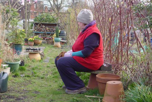 The gardener contemplates her garden.