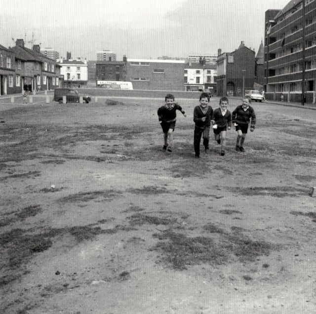 Benledi Street houses, O'Connor's pub and Woodstock Gardens. And in the centre, behind the children, the Benledi Street Housing office.