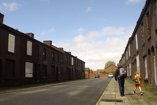 Father and son leave the Welsh Streets by walking along Powis Street.