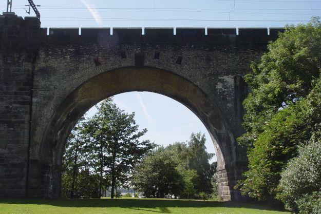 Through the arch of the rail bridge.
