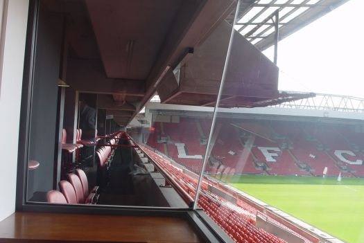 Whilst around us the great stadium listens.