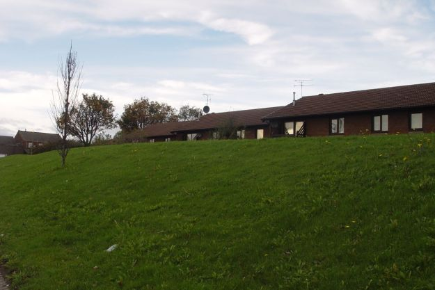 Pat 1980s housing built behind false hills.