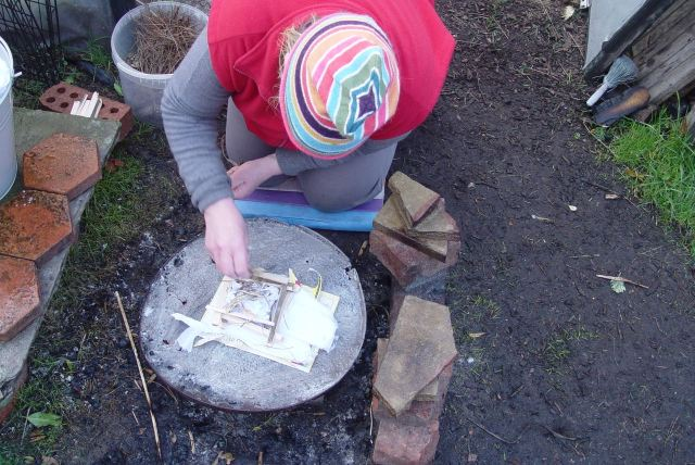 She begins building the fire for the cooking.