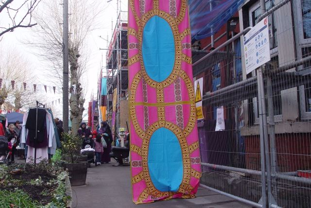Hanging tapestries from the Liverpool Mutual Homes scaffolding on this side of the street.
