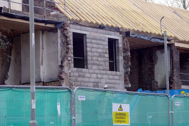 The collapsed rear walls being carefully replaced.