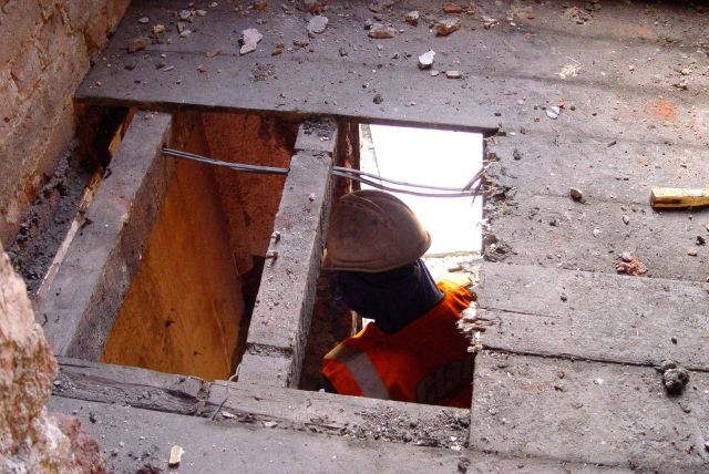 Looking through a hole in the floor to the works taking place downstairs.