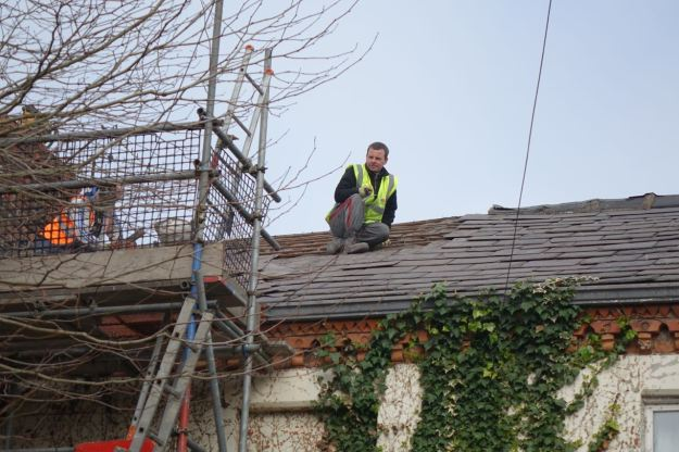 As the roof next to an occupied house is carefully stripped of its slates.
