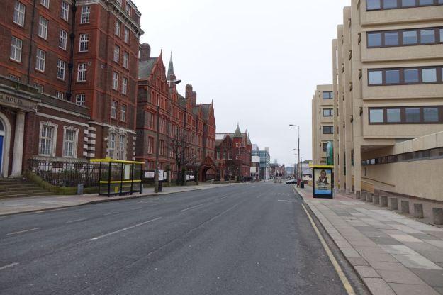 Walking along the empty road.