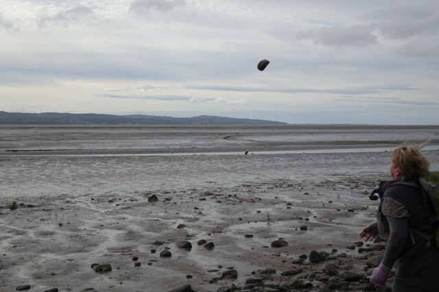 Sarah cheered herself up chucking stones out onto the mud.