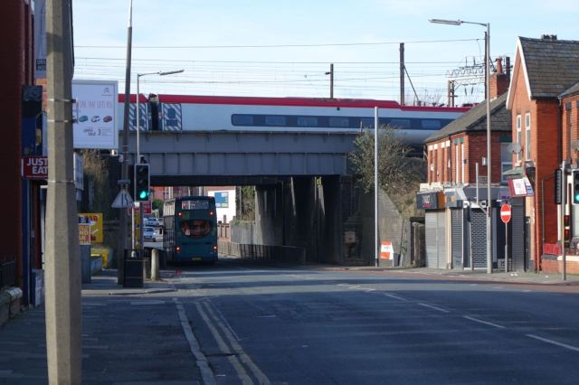 The inbound London train crosses a 79D bus on Picton Road.