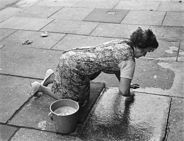 cleaning the pavement outside her home