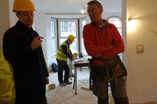 Joe from Assemble, back from Glasgow, talking with Dave the joiner, while his 16 year old apprentice Charlie works in the background.