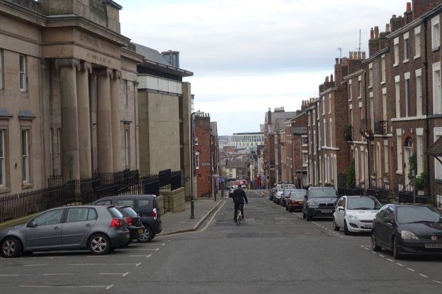 A lone and dress-suited cyclist on Mount Street.