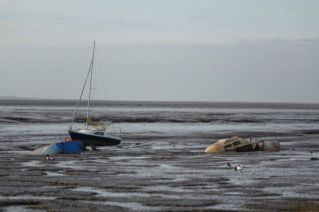 Noticing the boats waiting, all dilapidated, to be refloated by the next tide.